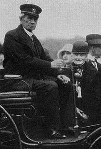 操舵柄を握るのが自動車発明者カール・ベンツ、隣が性能実証長距離走行を実行した妻ベルタ。
