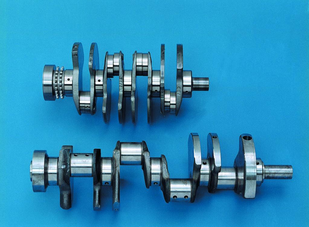いかにも短い5ベアリングのクランクシャフトに対向するバンクのコンロッド(8本)が装着される。クランクピンオフセットは高性能エンジンでおなじみの180度で、いわゆるシングルプレーン(あるいは平面クランク)。2次成分の振動に課題があるものの、出力向上には有利に働く。右側は一般的なV8エンジンのクランクシャフト。